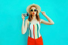 Colorful young woman holding retro camera, blowing red lips sends air kiss in summer straw hat having fun on blue wall stock photography
