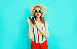 Colorful young woman holding retro camera, blowing red lips sends air kiss in summer straw hat having fun on blue wall stock image