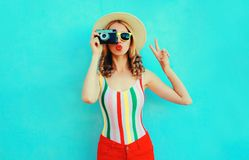Colorful young woman holding retro camera, blowing red lips sends air kiss in summer straw hat having fun on blue wall stock photos