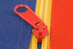 Colorful zipper on canvas. Red zipper on blue and yellow canvas Stock Photos