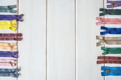 Colorful zippers on white wooden table. Rustic style. Needlework. Copy space. Crafts and Hobbies stock photo
