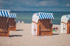 Colorfuled镶边了在沙滩的被顶房顶的椅子在特拉沃明德 一对被弄脏的夫妇坐海滩在背景中 吕贝克 库存照片