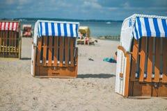 Colorfuled镶边了在沙滩的被顶房顶的椅子在特拉沃明德 一对被弄脏的夫妇坐海滩在背景中 吕贝克 免版税库存图片