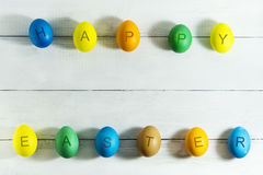 Colorfull ägg med den lyckliga påsken för inskrift på en vit träbakgrund Royaltyfri Foto