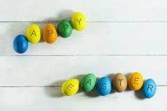 Colorfull ägg med den lyckliga påsken för inskrift på en vit träbakgrund Royaltyfria Foton