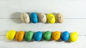 Colorfull ägg med den lyckliga påsken för inskrift på en vit träbakgrund Arkivfoton