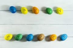 Colorfull ägg med den lyckliga påsken för inskrift på en vit träbakgrund Arkivbild