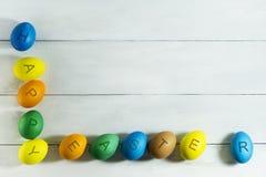 Colorfull ägg med den lyckliga påsken för inskrift på en vit träbakgrund Arkivfoto
