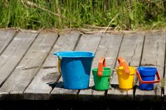 Colorfull buckets on the pier. Colorful playing buckets on wooden pier of lake Royalty Free Stock Image