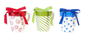 Colorfull ceramic mugs with bows on white Stock Photography