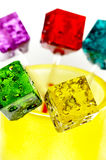 Colorfull dice lollipops. Bounch of colorfull translucent dice shaped lollipops backlit on white background Stock Photos