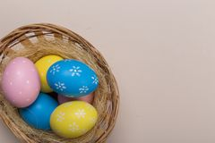 Colorfull easter eggs in nest on pastel color background with space. Concept royalty free stock images