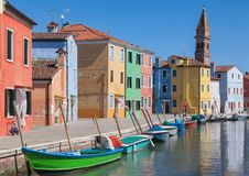 Colorfull facade Houses and bell tower on the island of Burano plus reflection in the water. Waterways with traditional boats Royalty Free Stock Photo