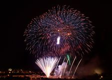 Colorfull fireworks explosion in the dark sky on the left side with the village silouthe on the bottom, popular fireworks show in Stock Photos