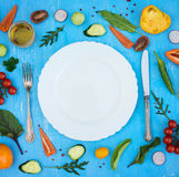 Colorfull fresh salad ingredients around empty white plate with. Silverware on light blue grunge background, top view, frame. Health salad making royalty free stock images