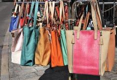 Colorfull handväskor hänger en presentoir Royaltyfria Bilder