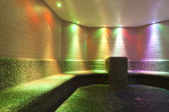 Colorfull illuminated steam bath in public swimmin. Colored lights in a steam bath with long tiled bench made with mosaic Stock Image