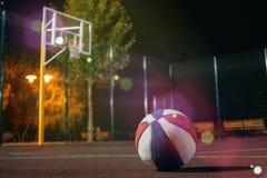 Colorfull koszykówki piłka z koszem i sieć na tle na półmrok czerwieni polu zdjęcie stock