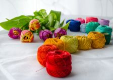 Needlework accessories. Colorfull needlework accessories on white background and bouquet of tulips Royalty Free Stock Photo