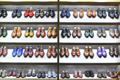 Colorfull pairs of shoes are exposed for sale. stock photo