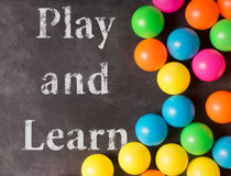 Colorfull plastic balls on the black chalkboard. Play and learn Stock Photos