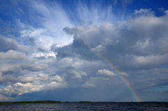 Colorfull rainbow under beaufitul cloud over lake. Video shows saturated and colorfull rainbow under beautiful cloud in the sky over lake's surface royalty free stock photography