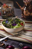 Colorfull Salad with Edible Flowers. Over a dark wooden table Stock Photography