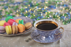 Colorfull sweet macaroons and cup of coffee. Colorfull and sweet macaroons and coop of coffee on a table on a table with xmas lights royalty free stock photo