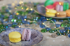 Colorfull and sweet macaroons on a table. On a table with xmas lights royalty free stock photography