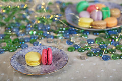 Colorfull and sweet macaroons on a table. On a table with xmas lights stock photo