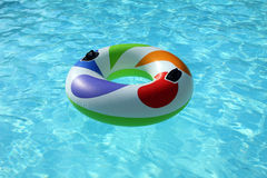 Swim ring floating on swimming pool. Colorfull swim ring floating on a blue swimming pool Royalty Free Stock Photography