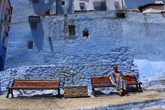 A colorfully clad woman relaxes in colorful Chefchaouen Royalty Free Stock Image