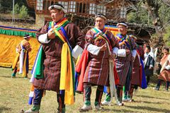 Yak Festival Participants Dance and Sing in Bhutan Village. Colorfully-costumed male participants dance and sing in local Yak Festival in rural Bhutan Stock Photo