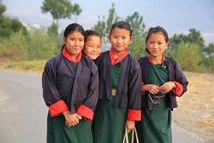 Happy Girl Students Heading for School in Bhutan. Colorfully-dressed students on their way to school in rural Bhutan Stock Image