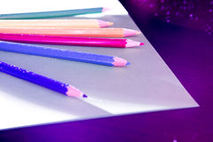 Colorfully Illuminated Colored Pencils. Colored pencils in colorful lighting Royalty Free Stock Photography