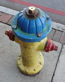 Colorfully Painted Fire Hydrant. Fire hydrant in yellow, red and blue against a gray sidewalk royalty free stock photography