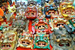 Colorfully painted traditional wood carving mask. Selling in the market, Bhutan Stock Photo