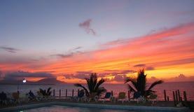 Colorfullzonsondergang op de oceaan met de wolken en de leunstoelen van het palmtrees zwembad royalty-vrije stock afbeeldingen