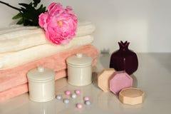 Colori bianchi e rosa del settingin del bagno Asciugamano, olio dell'aroma, fiori, sapone Fuoco selettivo, orizzontale Fotografia Stock