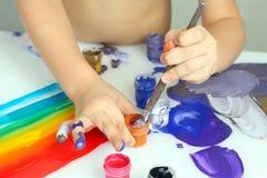 Colori della pittura di tiraggio della mano del ` s del bambino su un fondo bianco fotografia stock