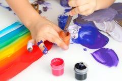 Colori della pittura di tiraggio della mano del ` s del bambino su un fondo bianco fotografia stock libera da diritti