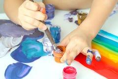 Colori della pittura di tiraggio della mano del ` s del bambino su un fondo bianco immagini stock libere da diritti