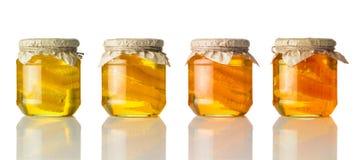 Colori differenti di miele in barattolo su fondo bianco Fotografie Stock