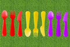 Colori i coltelli, i cucchiai e le forchette su erba verde, concetto di picnic Fotografia Stock Libera da Diritti
