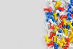 Colori i perni di spinta gruppo rosso, giallo, bianco e blu a destra di fondo bianco immagine stock libera da diritti