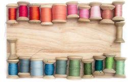 Colori il filo per il cucito sulle bobine su un di legno Immagini Stock