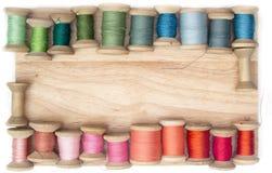 Colori il filo per il cucito sulle bobine su un fondo di legno, handcraft la vista superiore Fotografie Stock