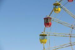 Colori le cabine di una ruota di ferris contro il cielo blu Immagini Stock Libere da Diritti