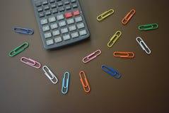 Colori le clip dei colori differenti con un calcolatore grigio su un fondo opaco marrone fotografia stock libera da diritti