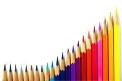 Colori le matite che coltivano la fila isolata su fondo bianco Immagine Stock